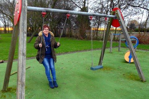 Nettie Spijker op de schommel in de speeltuin